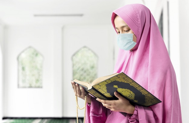 Donna musulmana asiatica in un velo e indossando la maschera antinfluenzale tenendo perline di preghiera e leggendo il corano