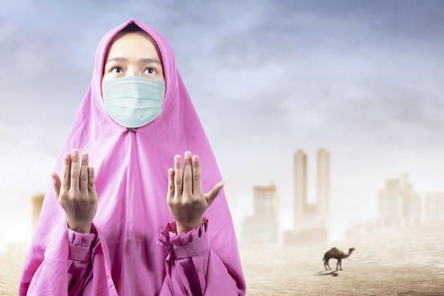 Donna musulmana asiatica in un velo e indossando maschera antinfluenzale in piedi mentre alzando le mani e pregando
