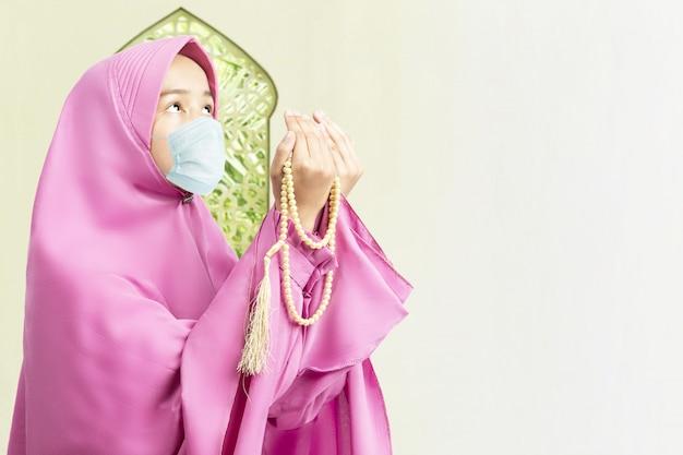 Donna musulmana asiatica in un velo e indossando maschera antinfluenzale in preghiera con perline di preghiera