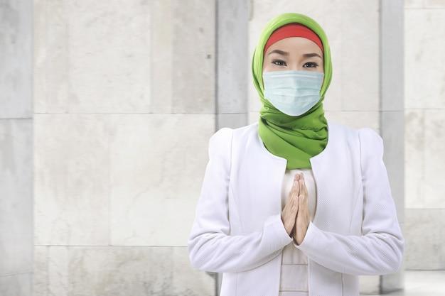 Donna musulmana asiatica in un velo e indossando preghiera maschera antinfluenzale