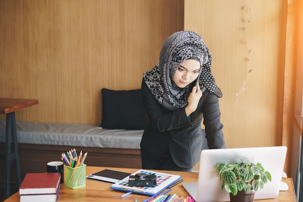 Donna musulmana asiatica occupata di affari che parla sul telefono cellulare e che utilizza computer portatile nell'ufficio moderno.