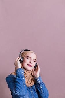 Donna musulmana che ascolta la musica sulle cuffie