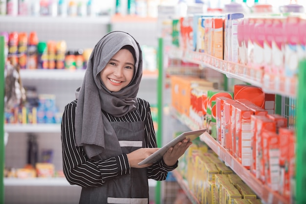 Donna musulmana che controlla il prodotto presso il negozio