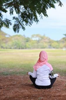Donna musulmana che si siede sull'erba e che gode della meditazione di yoga
