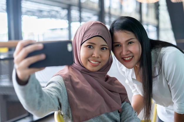 Donna musulmana che tiene smartphone e utilizzando la fotocamera anteriore per selfie scatto con amico