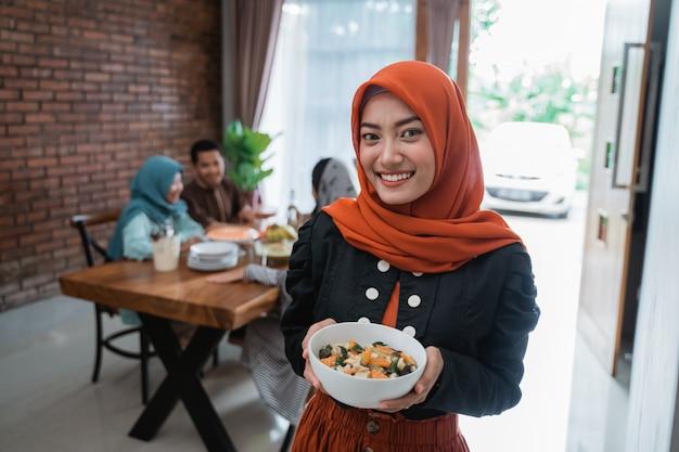 Donna musulmana con cibo servito per la famiglia