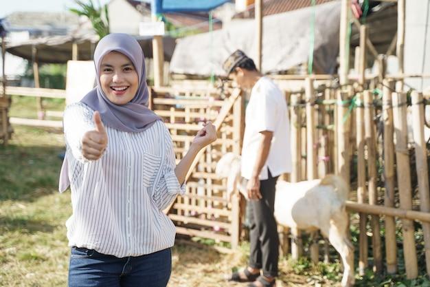 Donna musulmana con sciarpa che mostra il pollice in su mentre levandosi in piedi nell'allevamento di capre. concetto di eid adha