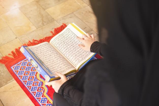 Donna musulmana del primo piano che legge corano, in moschea.