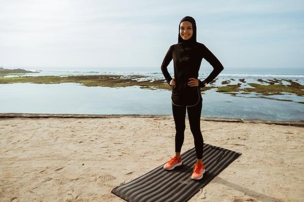 Donna musulmana di sport sull'esercitazione della spiaggia