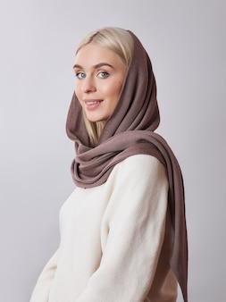 Donna musulmana europea con i capelli biondi in uno scialle di foulard vestito in testa