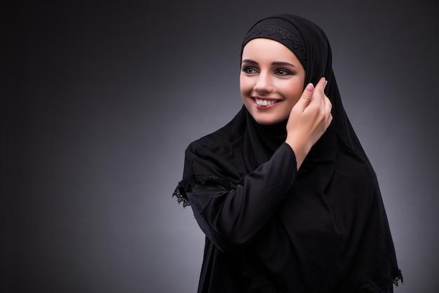 Donna musulmana in abito nero su sfondo scuro