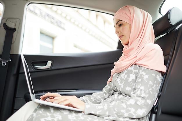 Donna musulmana nel lavorare al computer portatile in auto