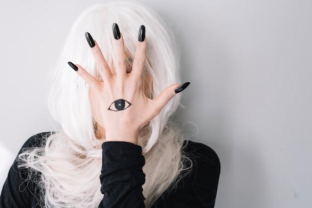 Donna, nascondersi, faccia, dietro, mano, tatuaggio