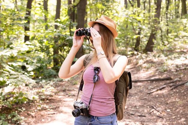 Donna nei boschi con il binocolo