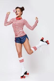 Donna nei pattini di rullo e con le cuffie e la lecca-lecca rosse