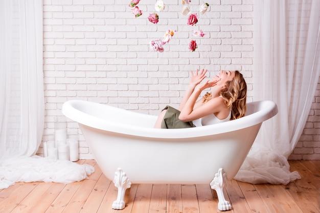 Donna nel bagno divertendosi con i fiori. bella giovane donna bionda che gode del bagno piacevole, osservando in su e sorridendo