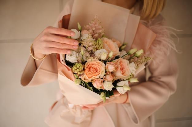 Donna nel cappotto che tiene un mazzo di colore cremoso e fiori bianchi