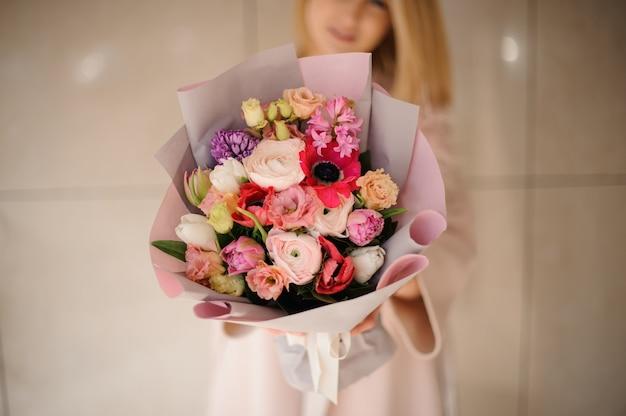 Donna nel cappotto che tiene un mazzo di fiori multicolori rosa teneri di colore