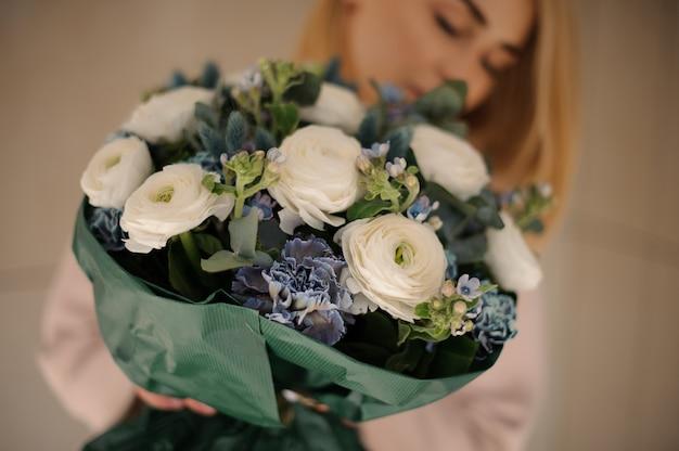 Donna nel cappotto che tiene un mazzo di teneri fiori bianchi e blu intenso