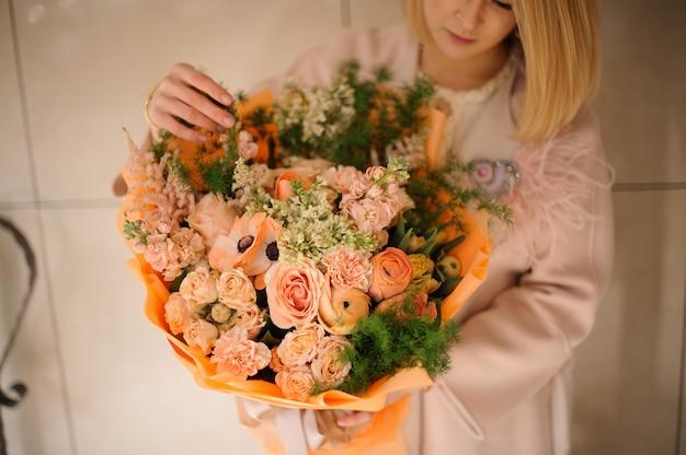 Donna nel cappotto che tiene un mazzo di teneri fiori color pesca