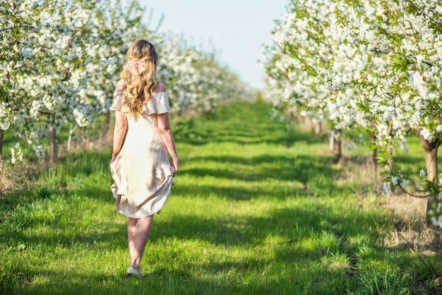 Donna nel frutteto di fioritura della ciliegia in primavera
