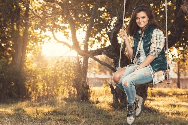 Donna nel parco al giorno soleggiato di autunno