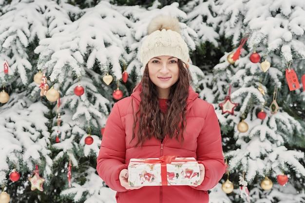 Donna nel parco di inverno con il contenitore di regalo. bella donna nella foresta nevosa di inverno. concetto di natale, di feste e di svago - giovane donna felice con il contenitore di regalo all'aperto in inverno