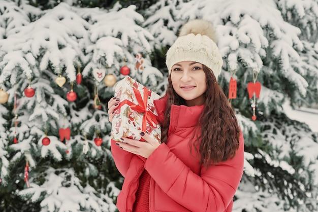 Donna nel parco di inverno con il contenitore di regalo. bella ragazza nella foresta nevosa di inverno. concetto di natale, di feste e di svago - giovane donna felice con il contenitore di regalo all'aperto in inverno