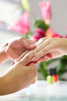 Donna nel salone del chiodo che riceve massaggio della mano