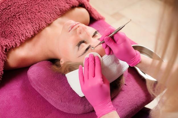 Donna nel salone di bellezza professionale durante una procedura di pulizia del viso