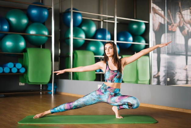 Donna nell'usura di sport che pratica yoga in palestra