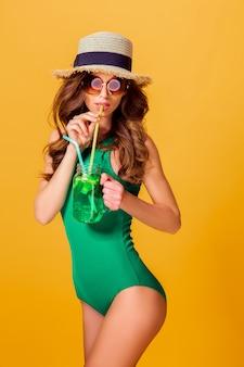 Donna nella bevanda della tenuta del costume da bagno
