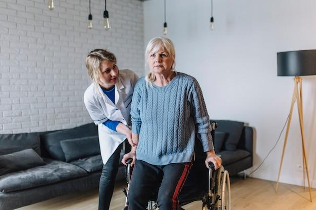 Donna nella casa di vecchiaia con sedia a rotelle