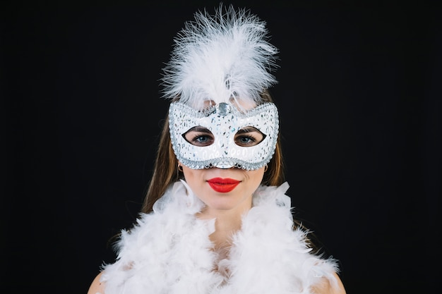 Donna nella maschera di carnevale che indossa la piuma di boa su fondo nero