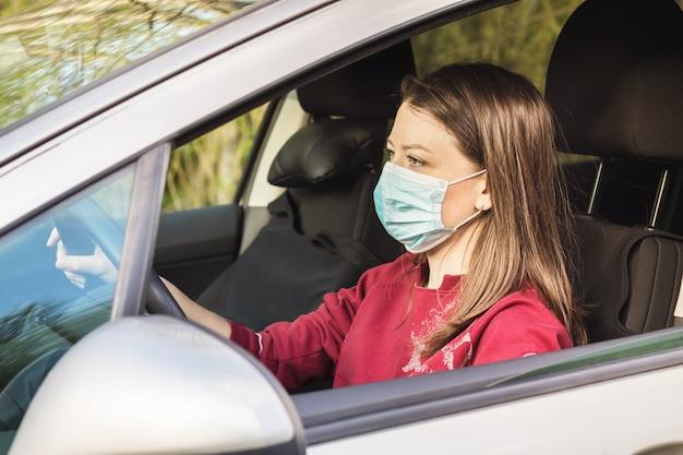 Donna nella mascherina medica che conduce un'automobile. signora mantenendo la distanza sociale.