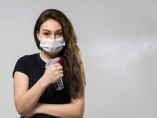 Donna nella mascherina medica sterile protettiva bianca che tiene spruzzo disinfettante speciale