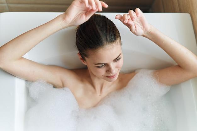 Donna nella vasca da bagno con schiuma bianca