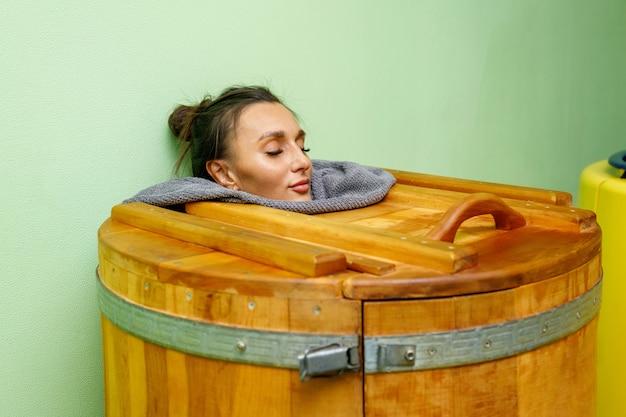 Donna nella vasca idromassaggio in legno