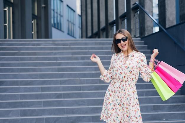 Donna nello shopping. ragazza giovane con borse della spesa colorate in giro per la città dopo lo shopping. consumismo, acquisti, shopping, concetto di stile di vita.