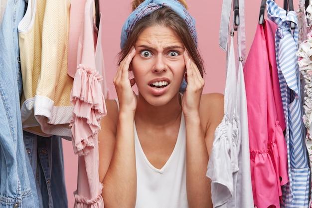 Donna nervosa che tiene le mani sul viso, guardando terrorizzata mentre si trova vicino al guardaroba con i vestiti, rendendosi conto che non ha nulla da indossare per l'incontro con gli amici. concetto di emozioni umane negative