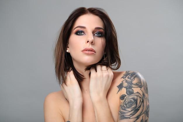 Donna nuda con tatuaggio in posa