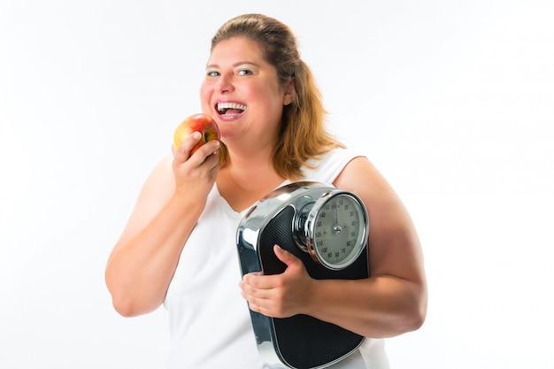 Donna obesa con scala sotto braccio e mela