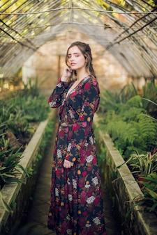Donna obliqua che posa in una serra