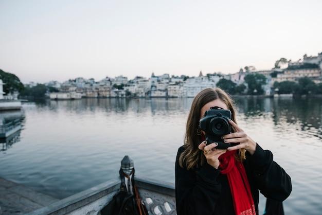 Donna occidentale che cattura una vista della città di udaipur, india