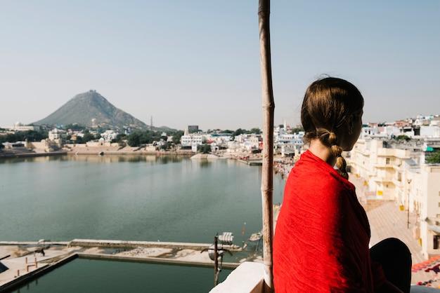 Donna occidentale che gode di una vista del lago pushkar nel rajasthan