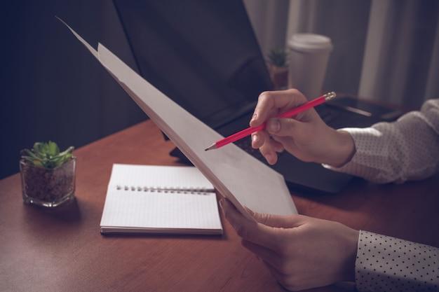 Donna occupata di affari che lavora con i documenti e che riferisce al posto di lavoro.