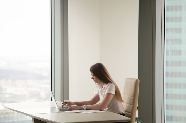 Donna occupata seria che lavora al computer portatile nell'interno dell'ufficio, copyspace