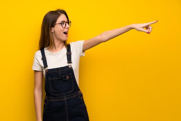 Donna oltre muro giallo che punta lontano