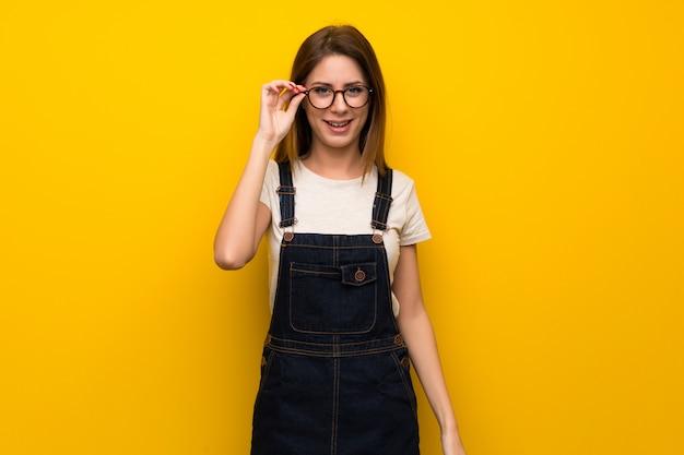 Donna oltre muro giallo con gli occhiali e sorpreso