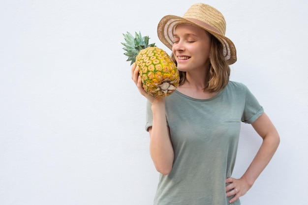 Donna pacifica felice in cappello di estate che odora intero ananas